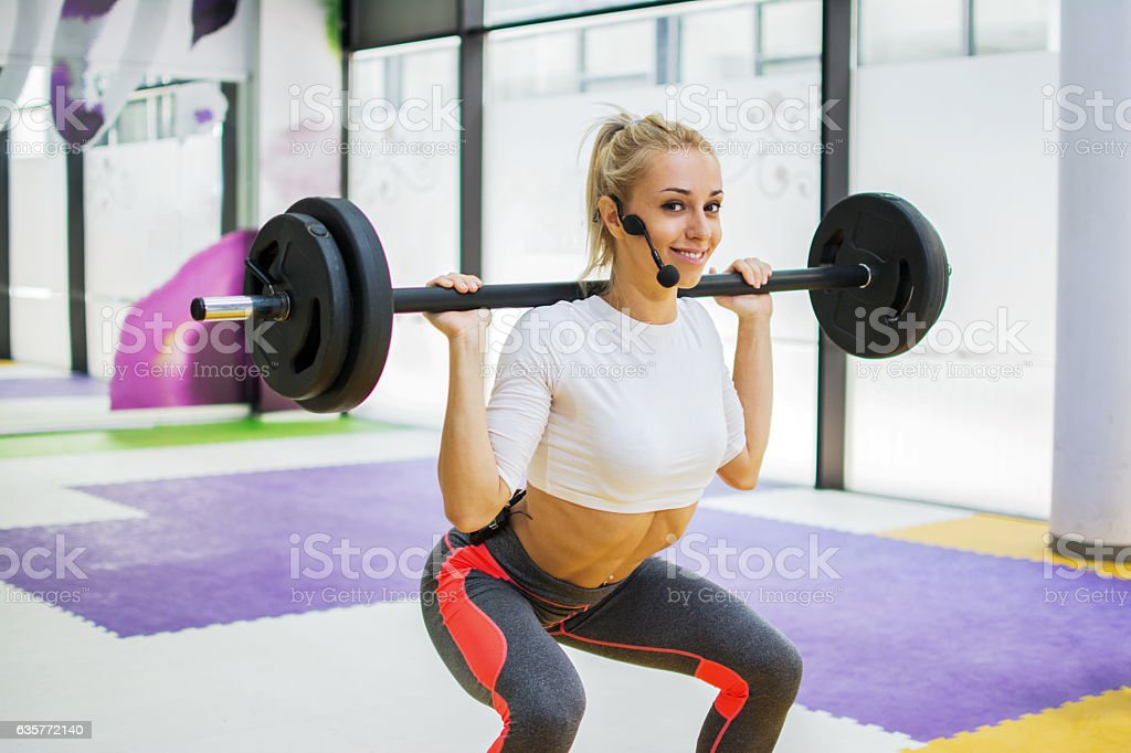 Sporty girl with microphone doing some squats with a barbell. - foto de stock