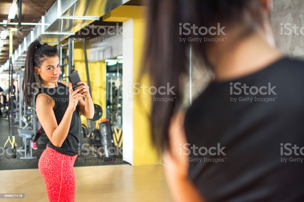 Sporty girl with smartphone taking mirror selfie in gym. stock photo