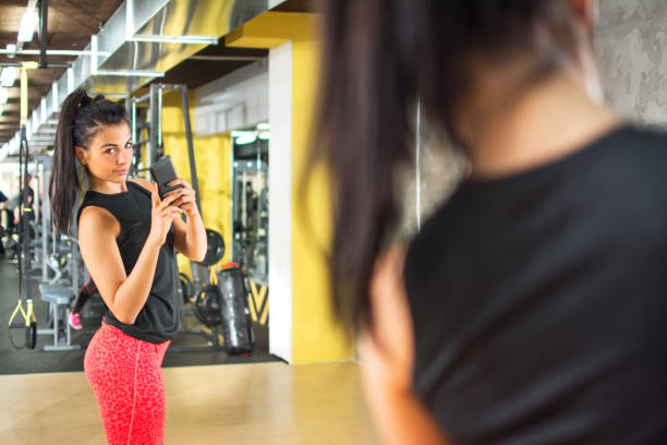 Sporty girl with smartphone taking mirror selfie in gym. Sporty girl with smartphone taking mirror selfie in gym. alternative pose stock pictures, royalty-free photos & images