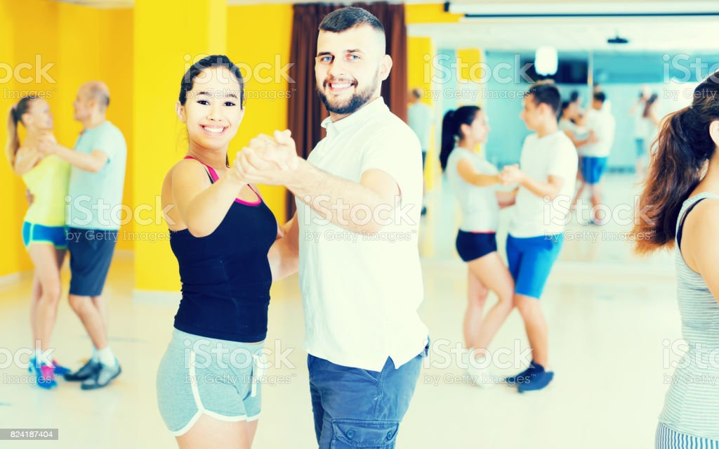 sporty girls and men learning salsa steps stock photo