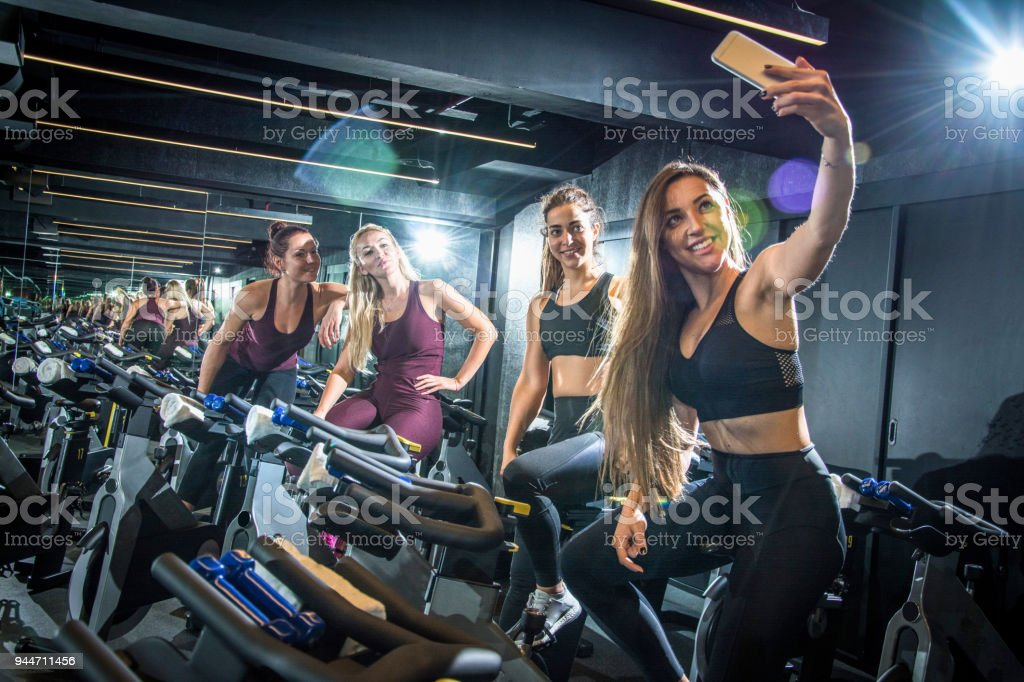 Sporty girls taking selfie while sitting on exercise bikes in gym stock photo