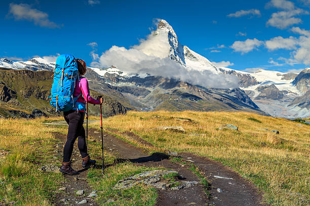 Sporty hiker woman with Matterhorn peak in background,Valais,Switzerland Hiker woman with backpack and mountain equipment,looking at view in Valais region,Matterhorn,Switzerland,Europe zermatt stock pictures, royalty-free photos & images