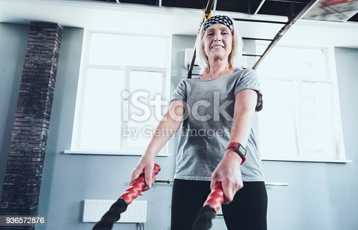 936573360 istock photo Sporty lady looking into camera while working with battling ropes 936572876