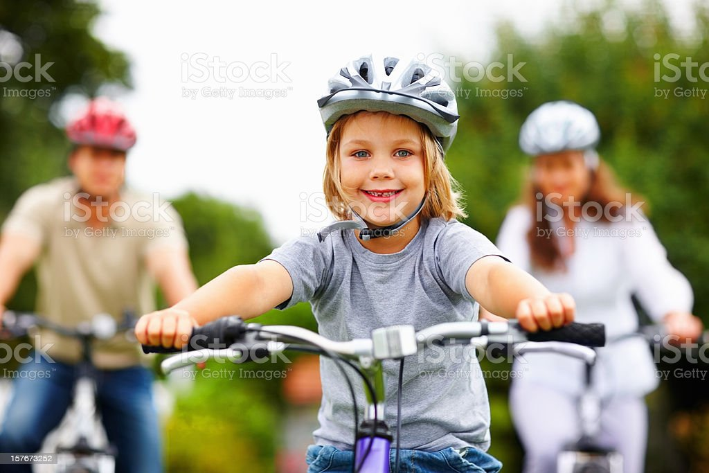 Sporty little boy with his parent in background riding bicycles royalty-free stock photo
