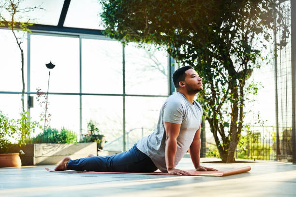 Sporty male in Urdhva Mukha Shvanasana pose Full length of man exercising on porch. Mid adult male is practicing Upward Facing Dog Pose. He is in sports clothing. sun salutation stock pictures, royalty-free photos & images