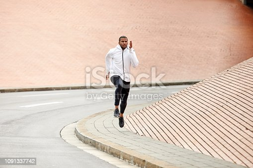 Full length of young sporty male jogging on roadside against wall. Man is running by road. He is representing healthy lifestyle in city.