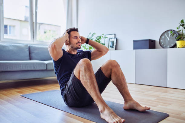 Sporty man doing sit-ups exercise during home workout stock photo