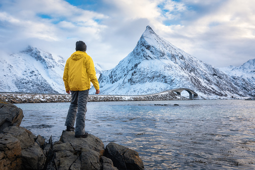 Sporty man in yellow jacket standing in the stone on seacoast against snowy mountains and cloudy sky at sunset in winter. Landscape with man, water, Fredvang bridge in Lofoten Islands, Norway.