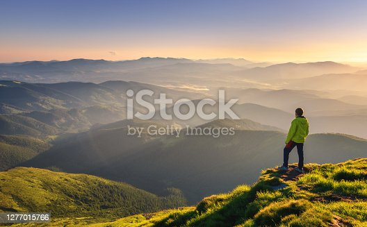 Sporty man on the mountain peak looking on mountain valley with sunbeams at colorful sunset in autumn in Europe. Landscape with traveler, foggy hills, forest in fall, amazing sky and sunlight in fall