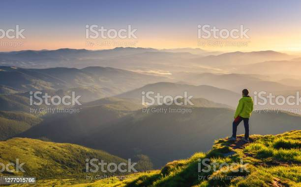 Photo of Sporty man on the mountain peak looking on mountain valley with sunbeams at colorful sunset in autumn in Europe. Landscape with traveler, foggy hills, forest in fall, amazing sky and sunlight in fall