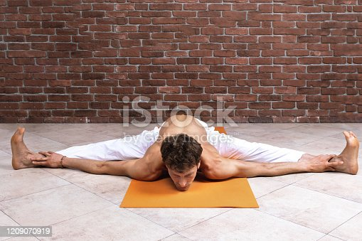 Sporty man practicing hatha yoga in studio. Male in white pants sitting in Wide-Angle Forward Bend pose, Upavishtha Konasana. Yogi, sport and healthy concept with copy space