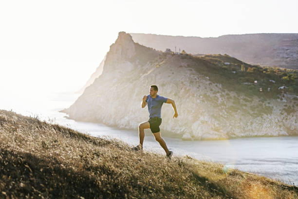 sporty man running mountain trail stock photo