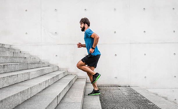 sporty man running up steps in urban setting - jogging stock pictures, royalty-free photos & images