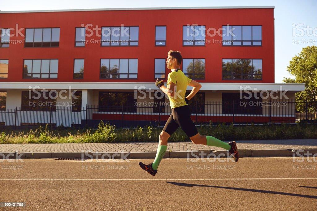 A sporty man runs through the streets zbiór zdjęć royalty-free