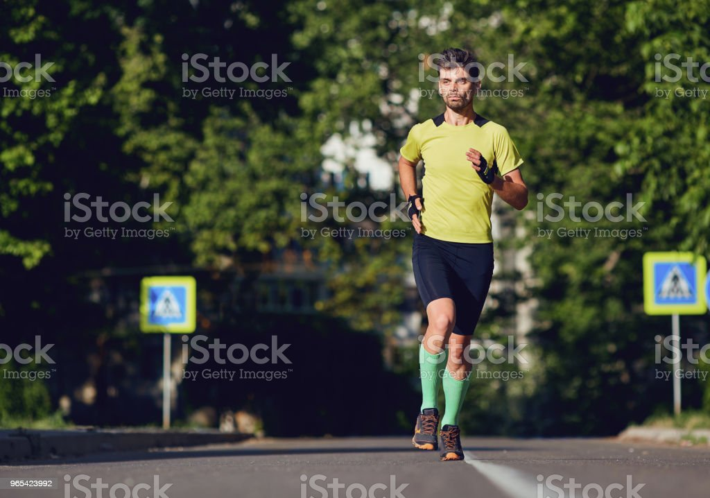 A sporty man runs through the streets zbiór zdjęć royalty-free