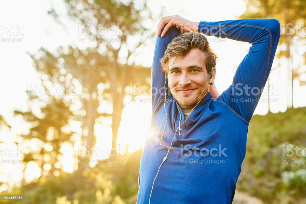 Sporty man stretching arm and shoulder outdoors stock photo