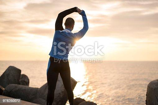 Photo taken on sunrise in Bulgaria, Eastern Europe. Sporty man stretching at the breakwater on sunrise.