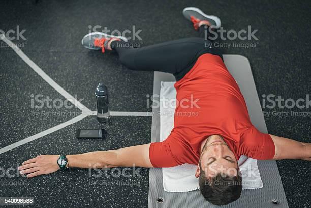 Sportlichen Mann Die Sich Vor Dem Fitnessstudiotraining Auf Der Matte Im Stockfoto und mehr Bilder von Dehnen