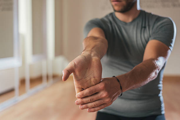 Sporty man stretching forearm before gym workout stock photo