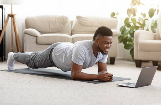 Sporty man training at home and watching online tutorial on laptop stock photo