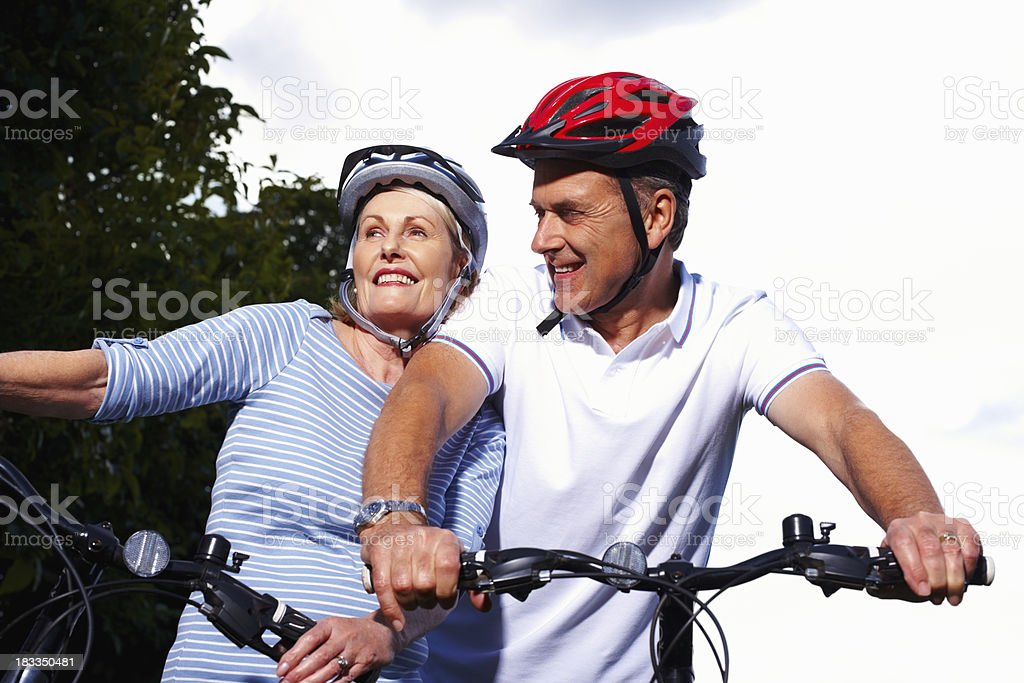 Sporty mature man and woman riding bicycles royalty-free stock photo