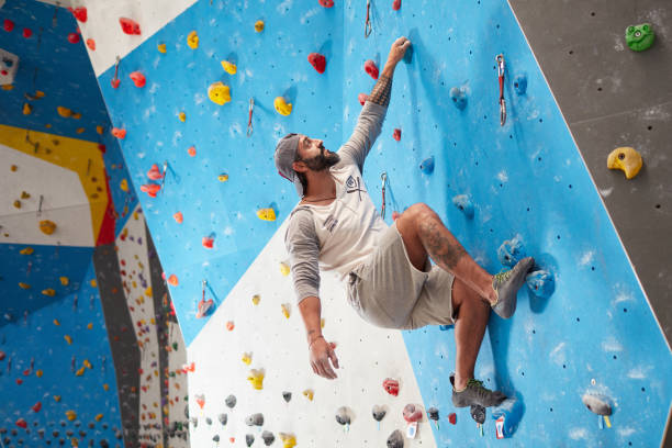 sporty mature man climbing wall in gym - arrampicata su roccia foto e immagini stock