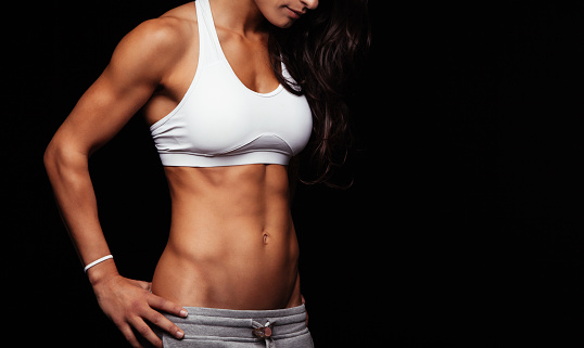 Fitness female model torso with her hands on hips. Female with perfect abdomen muscles standing against black background. Cropped shot with copyspace.