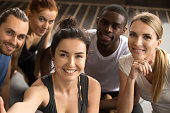 Sporty multiracial friends taking group selfie holding looking at camera