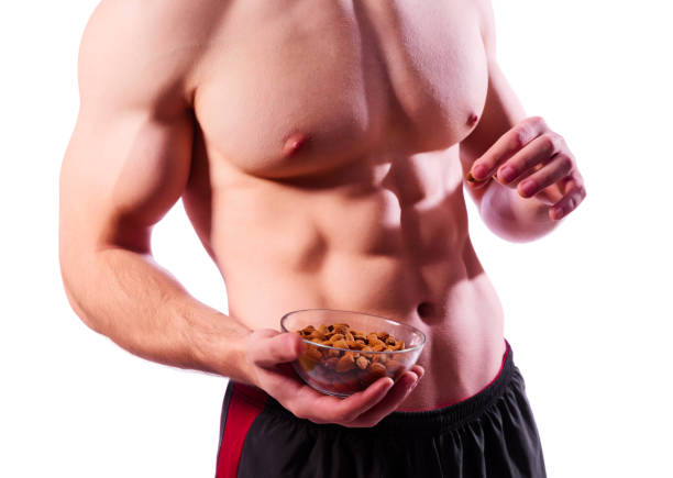 Sporty muscular man with almond nuts stock photo