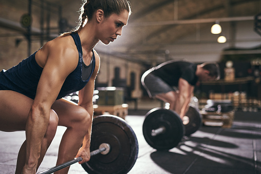 Fit people preparing to deadlift and holding barbells. Horizontal indoors shot