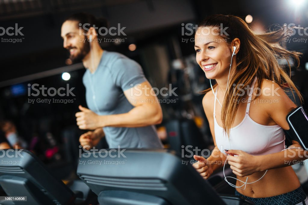 Sporty people running on treadmills in a health club stock photo
