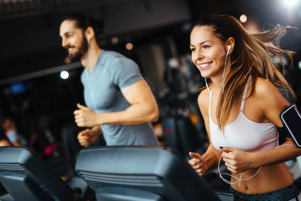 sporty people running on treadmills in a health club - palestre foto e immagini stock