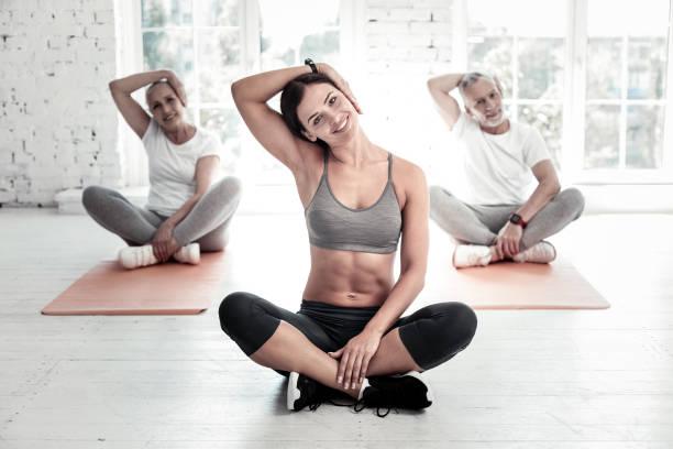 sportliche menschen dehnen hälse im fitnessclub - hals übungen stock-fotos und bilder