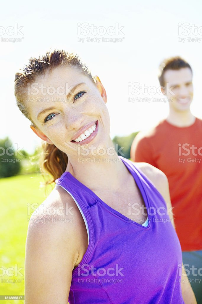 Sporty, pretty woman with man in the background royalty-free stock photo