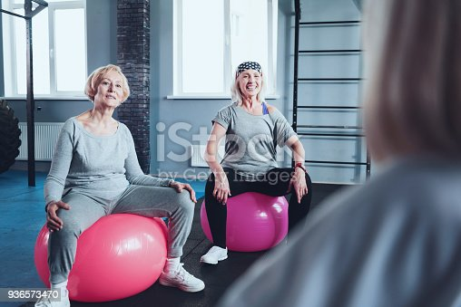 936573360 istock photo Sporty retired ladies sitting on fitness balls while training 936573470