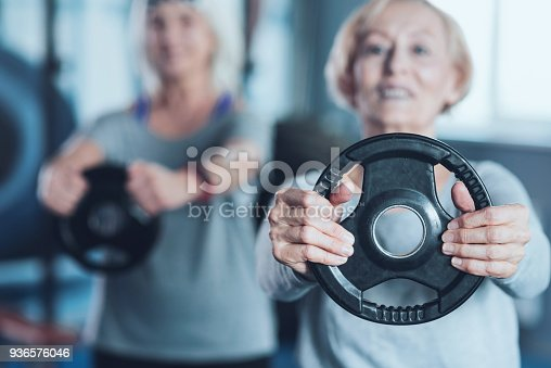 936573360 istock photo Sporty retired lady holding weight disk at fitness club 936576046