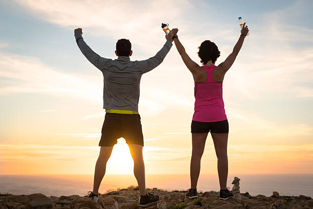 sporty runner couple rising arms in victory sign - trainingsplan frauen stock-fotos und bilder
