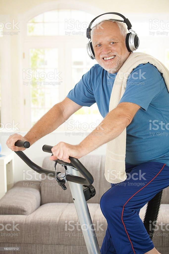 Sporty senior listening to music while exercising royalty-free stock photo