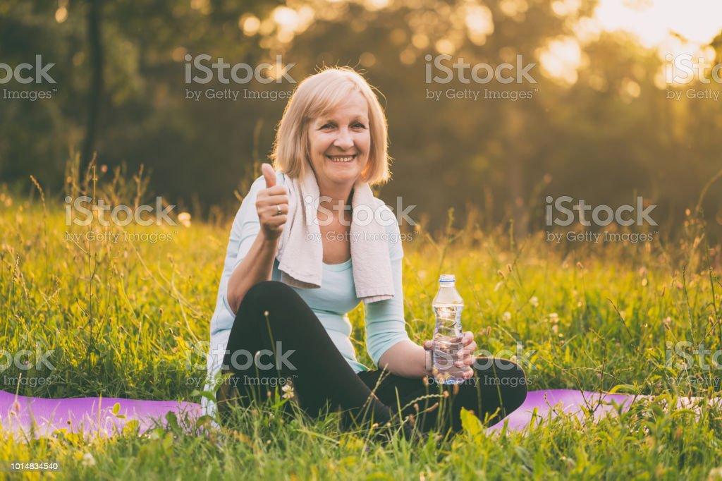 Sportliche senior Frau Trinkwasser und Daumen auftauchen – Foto