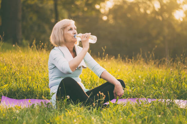 Sportliche senior Frau Trinkwasser – Foto