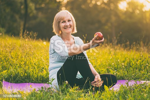 istock Sporty senior woman eating apple 1014834630