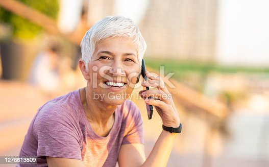 Portrait of a sporty senior woman sitting by the riverbank and talking on the mobile phone