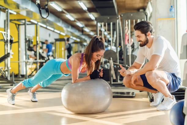 sportieve lachende vrouw planken op pilates bal terwijl haar persoonlijke trainer gehurkt naast haar en juichen voor haar doen. - personal trainer stockfoto's en -beelden