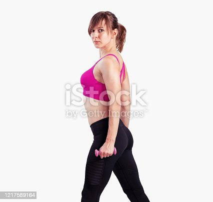 930998708 istock photo Sporty woman does the exercises with dumbbells on gray background. Photo of muscular woman in sportswear at studio 1217589164