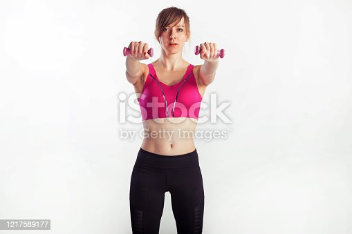 930998708 istock photo Sporty woman does the exercises with dumbbells on gray background. Photo of muscular woman in sportswear at studio 1217589177