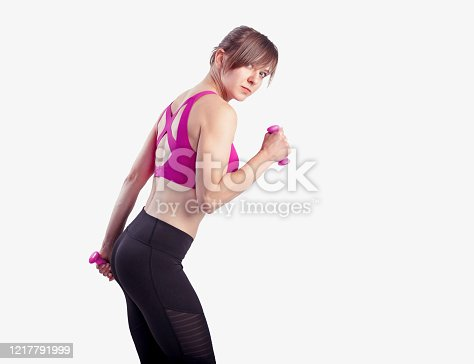 930998708 istock photo Sporty woman does the exercises with dumbbells on gray background. Photo of muscular woman in sportswear at studio side view 1217791999