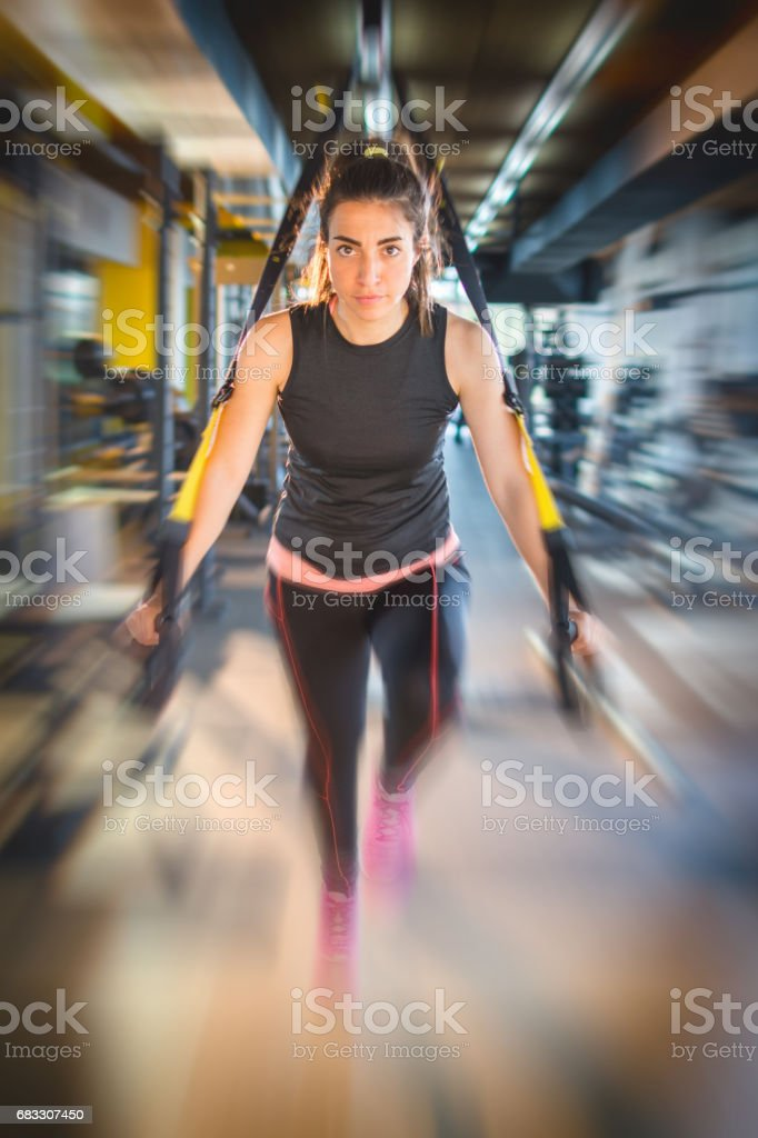 Sporty woman doing arm exercises with suspension straps at gym. Blurred motion effect. zbiór zdjęć royalty-free