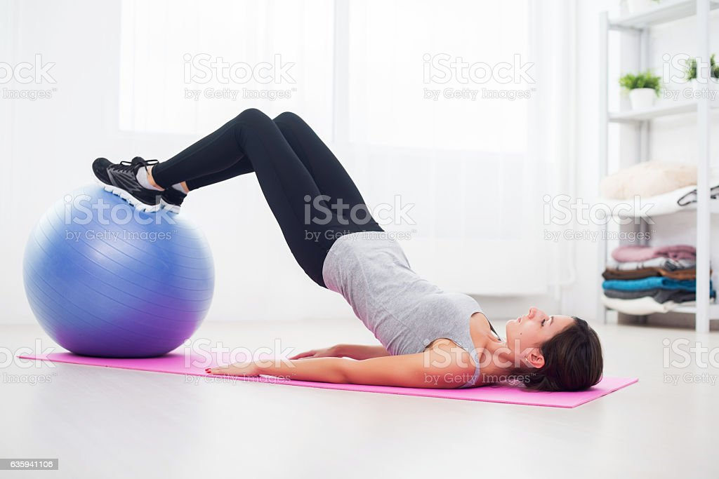 sporty woman doing pilates exercise lifting her pelvis with fit stock photo