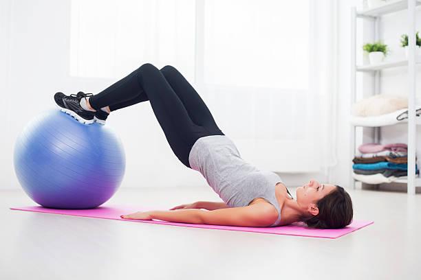 sporty woman doing pilates exercise lifting her pelvis with fit - bekken stockfoto's en -beelden