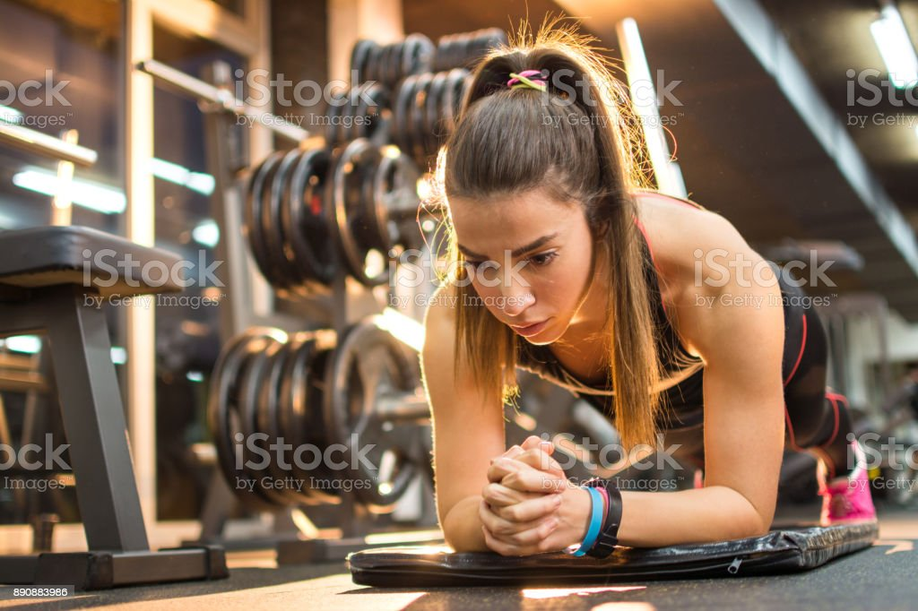 Sporty woman doing plank exercise in gym. stock photo